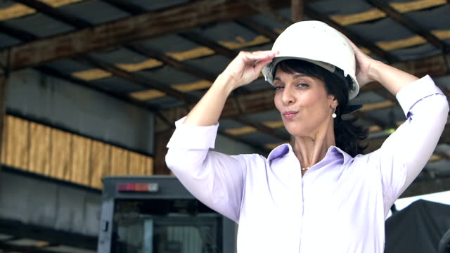 Hispanic woman puts on hardhat in warehouse