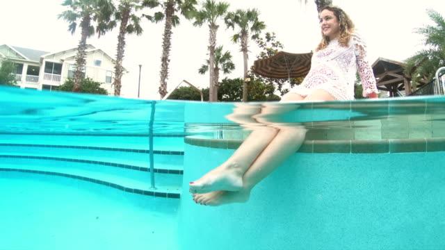 Mulher hispânica relaxante piscina, pés na água