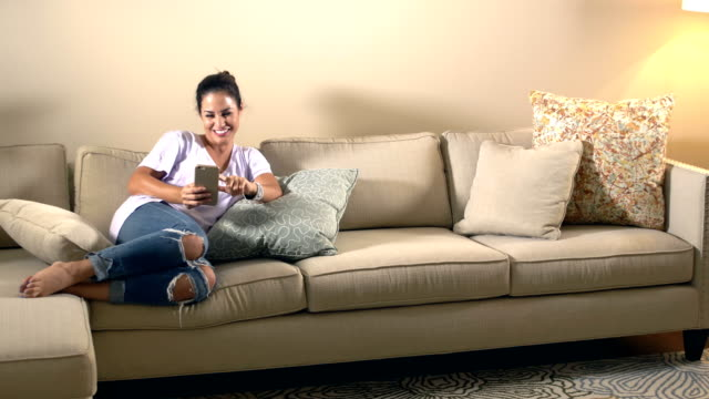 hispanic woman relaxing on coach, using smart phone - pillow stock videos and b-roll footage