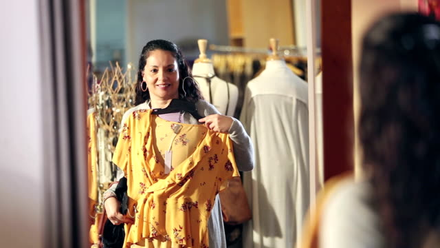 hispanic woman shopping in clothing store, at mirror - top capo di vestiario video stock e b–roll