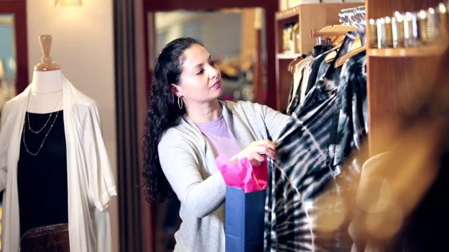 vídeos de stock, filmes e b-roll de compra latino-americano da mulher na loja de roupa - top