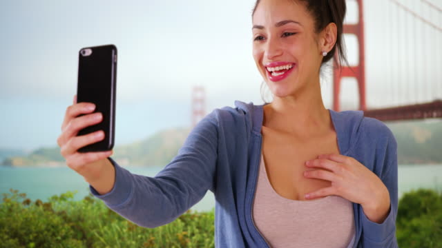 a hispanic woman takes a selfie near the golden gate bridge - 説得点の映像素材/bロール