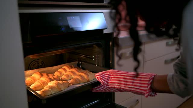 vidéos et rushes de femme hispanique prenant des croissants cuits au four hors du four - son