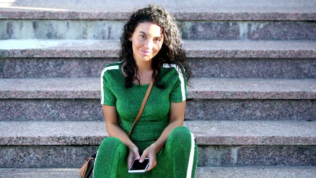 vidéos et rushes de la femme hispanique marche en bas de l'escalier, s'assied sur l'étape inférieure - vêtement de sport