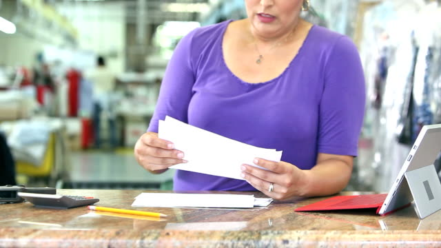 hispanic woman working at dry cleaners paying bills - launderette stock videos and b-roll footage
