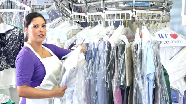 hispanic woman working at dry cleaners - launderette stock videos & royalty-free footage