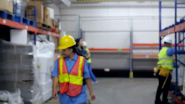 Hispanic Frau arbeitet in warehouse geht in den Mittelpunkt und Lächeln in die Kamera.