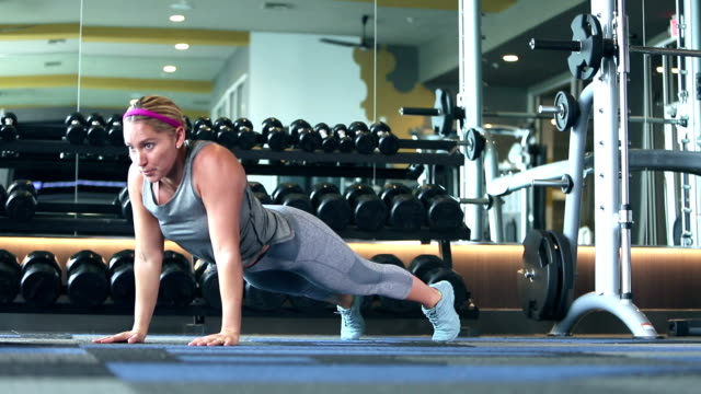 hispanic woman working out at gym, plank exercise - bending stock videos & royalty-free footage