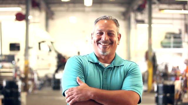 hispanic worker in trucking industry, smiling at camera - rivolto verso l'obiettivo video stock e b–roll