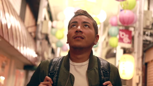 hispanic young man visiting old market in kyoto - tradizione video stock e b–roll