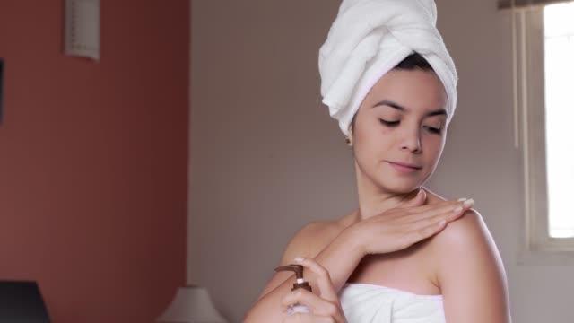 入浴した後、彼女の体に保湿クリームを適用するヒスパニック系の若い女性 - 頭点の映像素材/bロール