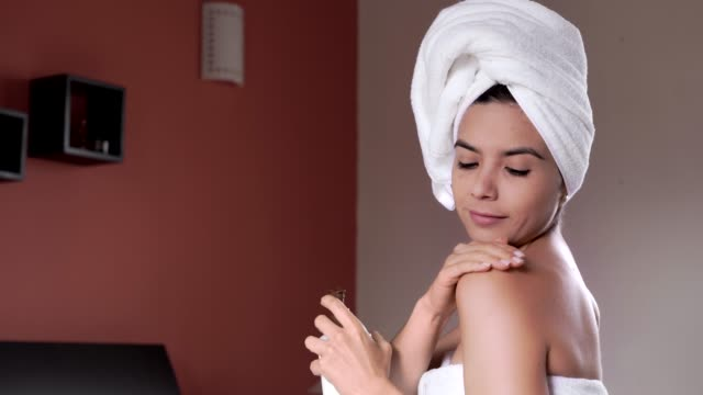 hispanic young woman applying moisturizing cream on her body after taking a bath - human head stock videos & royalty-free footage