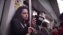 Hispanic young woman text messaging and using mobile phone while traveling in the train or subway