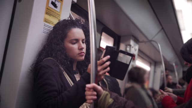 hispanic young woman text messaging and using mobile phone while traveling in the train or subway - underground rail stock videos & royalty-free footage