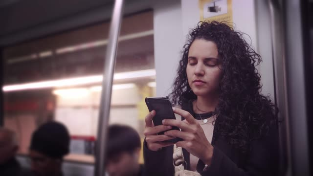 vídeos de stock e filmes b-roll de hispanic young woman text messaging and using mobile phone while traveling in the train or subway - mobilidade