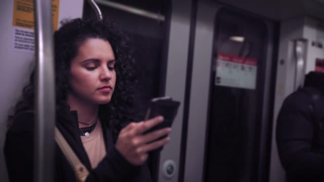 hispanic young woman text messaging and using mobile phone while traveling in the train or subway - public transport stock videos & royalty-free footage
