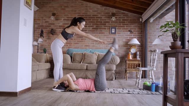 vídeos de stock, filmes e b-roll de mulheres jovens hispânicas ajudando umas às outras enquanto se exercitam em casa - corpo humano