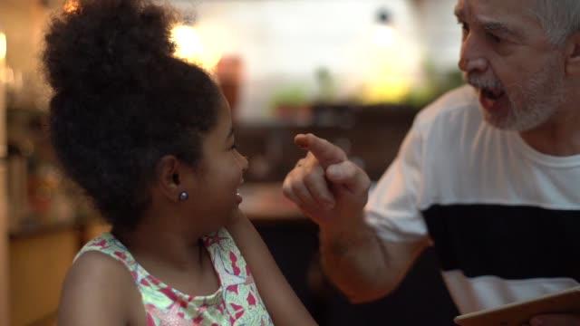 vidéos et rushes de grand-père hispanique-latino, apprendre à cuisiner à la maison - leurs petits-enfants qu'ils préparent brigadeiro brésilien - grand père