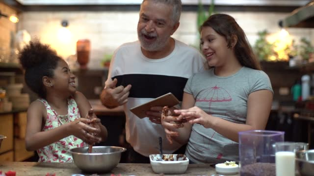 vídeos de stock, filmes e b-roll de hispano-latino avô ensinar o neto a cozinhar em casa - eles estão preparando o brigadeiro brasileiro - cozinha