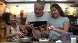 Hispanic-latino grandfather teaching their grandchild how to cook at home - They are preparing Brazilian Brigadeiro