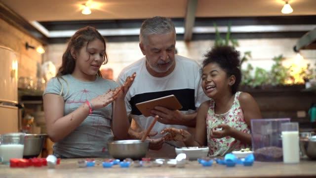vídeos y material grabado en eventos de stock de hispanic-latino abuelo enseña a su nieto a cocinar en casa - están preparando brasileño brigadeiro - 65 69 años