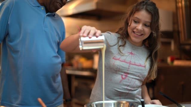 hispanic-latino grandfather teaching their grandchild how to cook at home - they are preparing brazilian brigadeiro - condensed milk stock videos & royalty-free footage