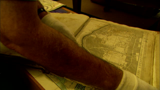 vídeos de stock, filmes e b-roll de a historian's hands wearing protective gloves turns pages in a book of maps. - cartografia