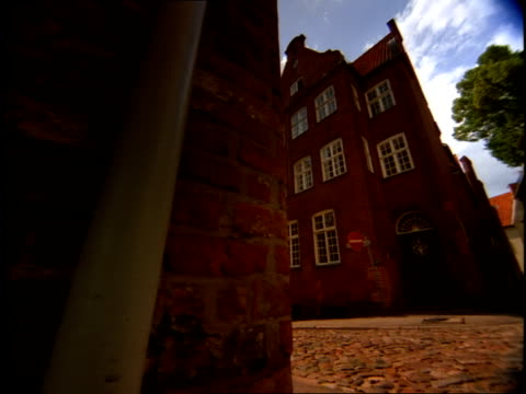 historic brick buildings rise above a winding cobblestone street in lubeck, germany. - lübeck stock-videos und b-roll-filmmaterial