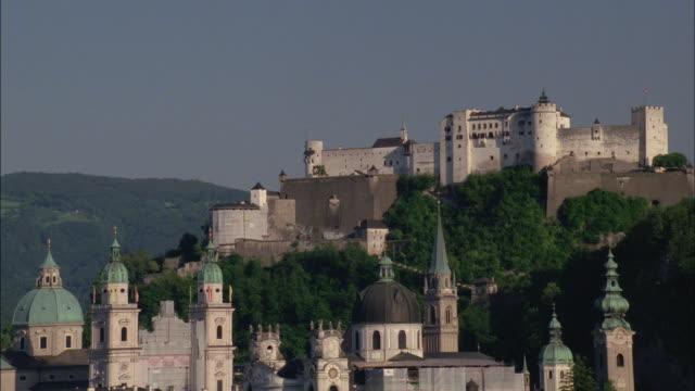 historic buildings sprawl up a hillside. - castello video stock e b–roll