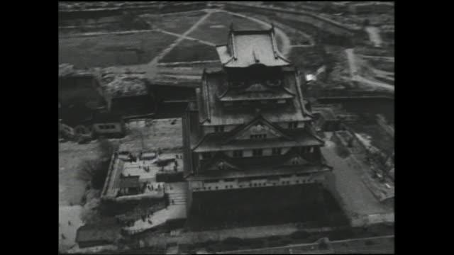 vídeos de stock e filmes b-roll de historic osaka castle towers above the adjacent park. - vala