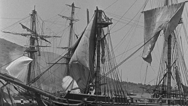 historic reenactment - film montage of sailing ships firing cannons while sailing in sea, men working on mast of sailing ships in sea - 1945 stock videos & royalty-free footage