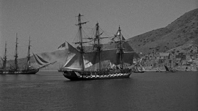 historic reenactment - film montage of sailing ships firing cannons while sailing in sea, american flag with 15 stars and 15 stripes waving on sailing ship in sea - 1945 stock videos & royalty-free footage