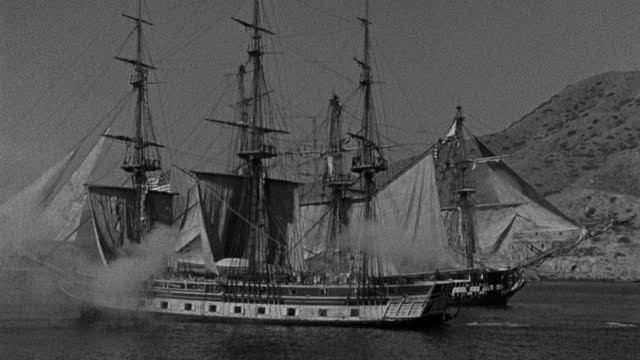 historic reenactment - wide shot of sailing ships firing cannons while sailing in sea - 1945 stock videos & royalty-free footage