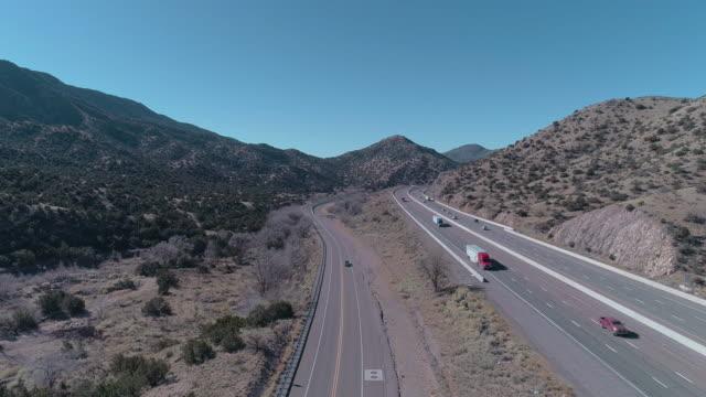 vidéos et rushes de route historique 66 et autoroute moderne 40 près de tijeras, entre les montagnes couvertes par la forêt nationale de cibola, non loin d'albuquerque, nouveau-mexique. vidéo de drone aérien avec le mouvement avant de caméra - route 66