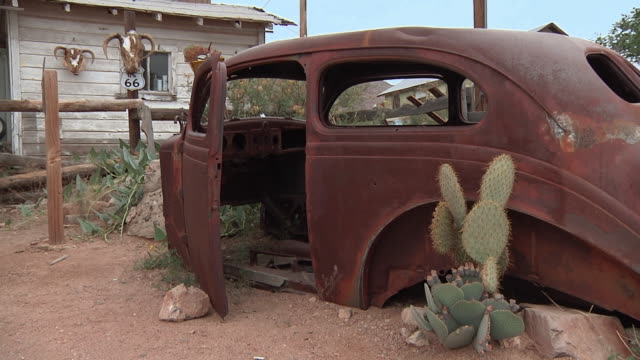 MS Historic Route 66 Signage at vintage gas station, rusted car with cactus growing out of it