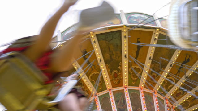 "stockvideo's en b-roll-footage met historic vintage chain swing carousel on the ""oide wiesn"", unrecognisable blurred people spinning seen from below - zweven"