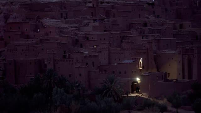 vidéos et rushes de complexe historique de aït benhaddou. vieux village de brique sur le désert de nuit - maroc