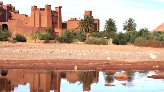 vídeos y material grabado en eventos de stock de complejo histórico de aït benhaddou. vieja aldea de ladrillo en el desierto. día soleado - oasis desierto
