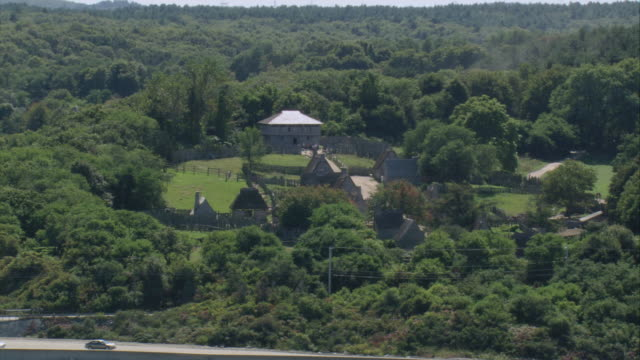 AERIAL Historical cottages at Plimoth Plantation near the Cape Cod shoreline / Plymouth, Massachusetts, United States