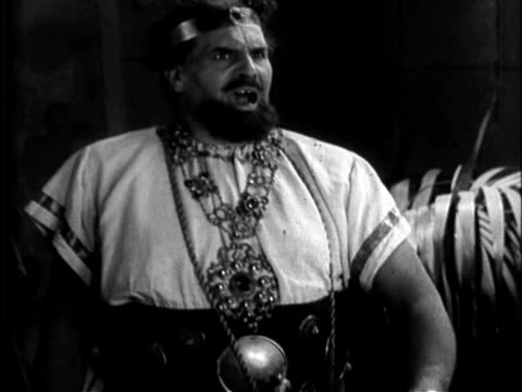 Historical reenactment of ancient Rome harvested from early silent film adaptation of Shakespeare's play Julius Caesar / rotund Brutus wearing Roman...