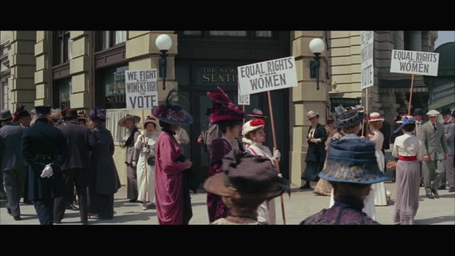ws historical reenactment, suffragette demonstration, women carrying 'votes for women' placards / usa - 投票点の映像素材/bロール