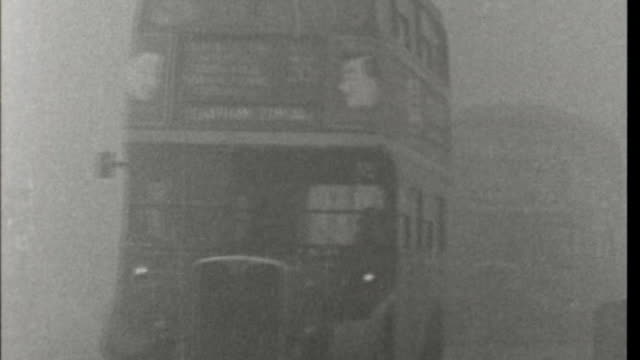 vidéos et rushes de history of smog in london; lib / tx 6.1.1956 london: ext b/w double decker buses along in thick smog - smog