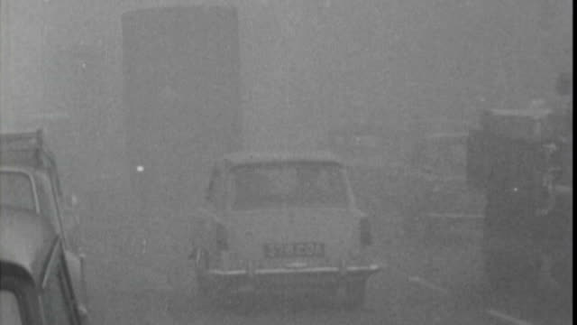 vidéos et rushes de history of smog in london x05106602 / 1966 w footage traffic along in thick smog people along covering their faces - smog