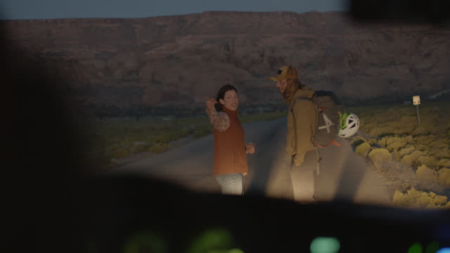 vidéos et rushes de hitchhiker stands in car headlights and gets a ride from friendly young woman on scenic mountain backroad at dusk. - règle de savoir vivre