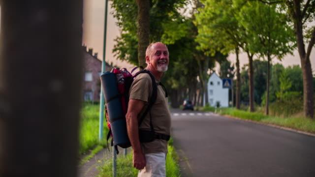 trampen senior reisende versucht, ein auto auf der straße zu stoppen - rucksack stock-videos und b-roll-filmmaterial