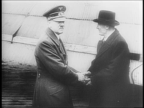 vidéos et rushes de hitler and mussolini's first meeting in 1934/ they shake hands and stand behind a rope in front of palm trees both in civilian clothes/ 1943 plane... - 1934