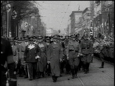 stockvideo's en b-roll-footage met hitler goering and military entourage walk down street lined with swastika flags / sudetenland czechoslovakia - 1938