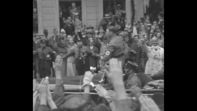 vídeos de stock e filmes b-roll de hitler rides in open car through street crowded with cheering soldiers and civilians he stands to wave then sits again as car drives on / standing in... - 1931