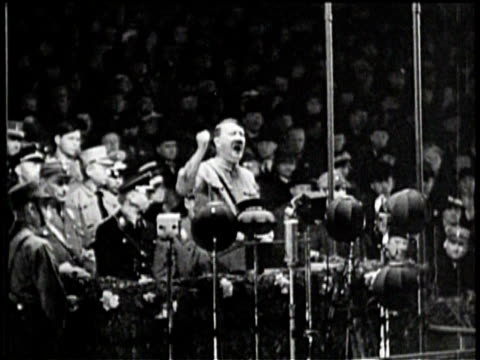 vídeos de stock, filmes e b-roll de hitler shouts into microphone and shakes his fist / a crowd is in attendance / german soldiers march / flag of germany - adolf hitler