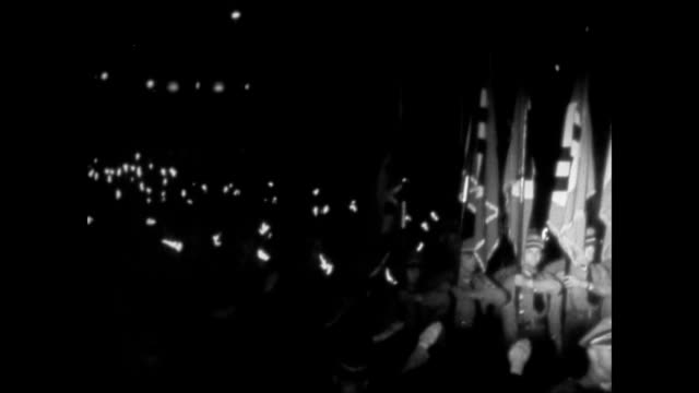 hitler standing w/ arm in salute nazi soldiers marching amp carrying flags in front of soldiers w/ torches ws hitler giving speech at podium placing... - 1936 stock-videos und b-roll-filmmaterial